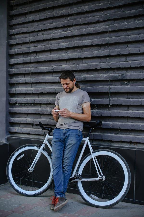 Парень с велосипедом и исправляет телефон стоковая фотография rf
