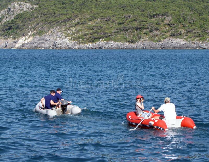 Парень с девушкой в красном раздувном rowing шлюпки на море Середины спасения от оборудования круиза плавать тускло Остатки на th стоковое фото rf