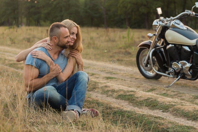 Парень с девушкой в поле на мотоцикле стоковые фото