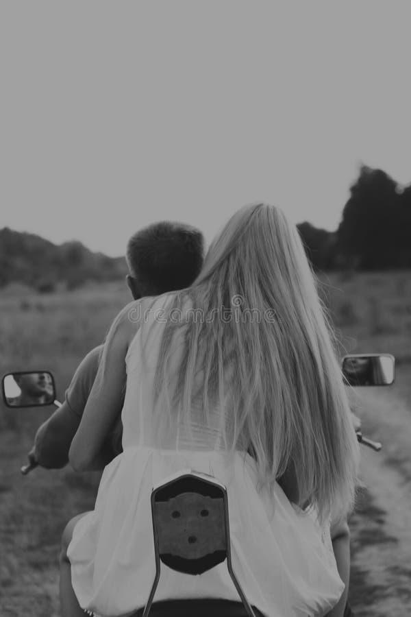 Парень с девушкой в поле на мотоцикле стоковое изображение rf
