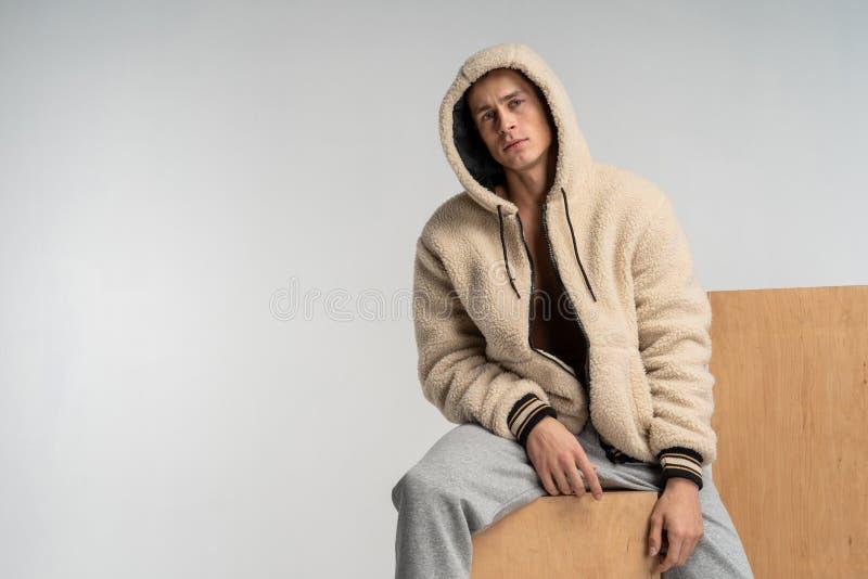 Парень с нагим торсом в серых брюках сидя на деревянном кубе стоковое фото rf
