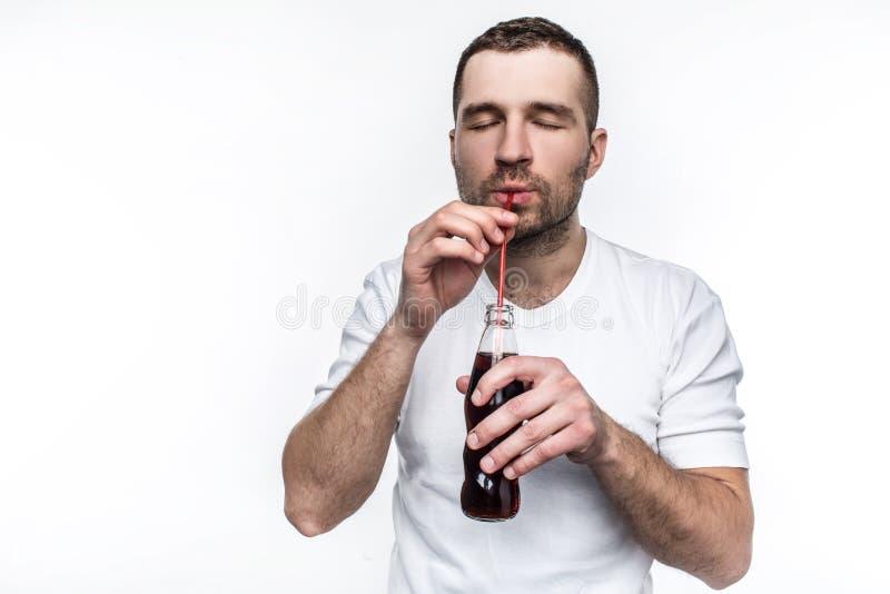 Парень с сокращения выпивает кокс от бутылки через солому Этот человек любит съесть фаст-фуд и выпить помадку стоковые фото