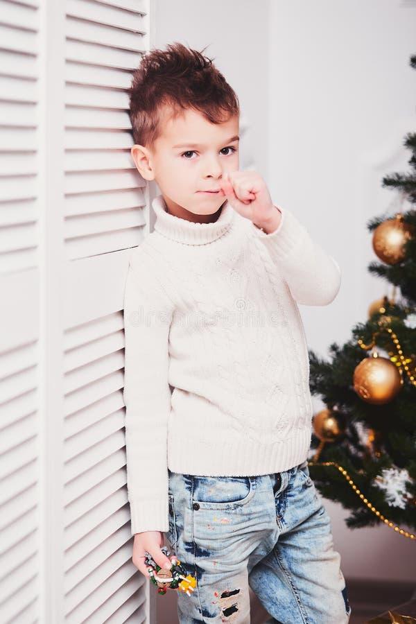 Парень с стильной iroquois стрижкой и в модных современных одеждах стоит около белой стены рядом с рождественской елкой A.C. стоковая фотография rf