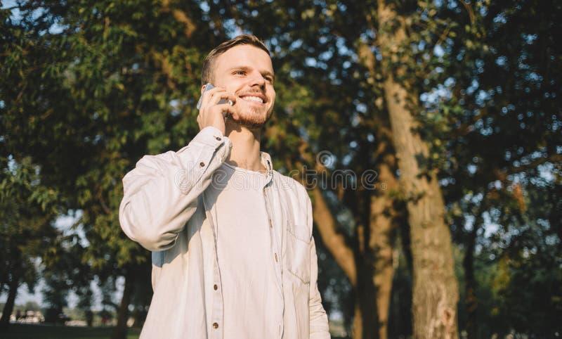 Парень с телефоном в парке стоковые изображения