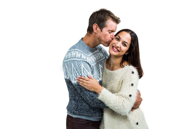 Парень целуя подругу пока стоящ стоковая фотография
