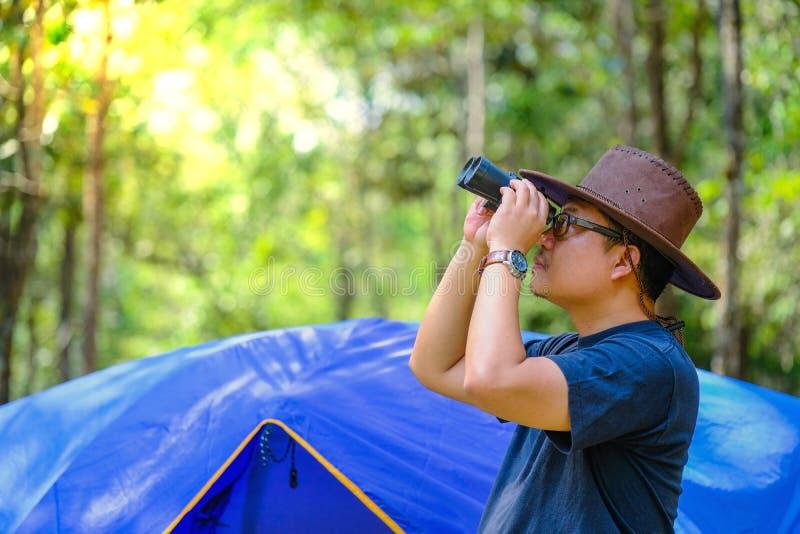 Парень Hiker смотрит в биноклях наслаждаясь птицей захватывающего вида стоковое изображение