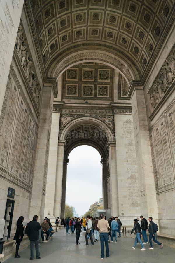 Париж, Франция - 2-ое апреля 2019: туристы под сводом Триумфальной Арки триумфальным в Champs-Elysees стоковые изображения