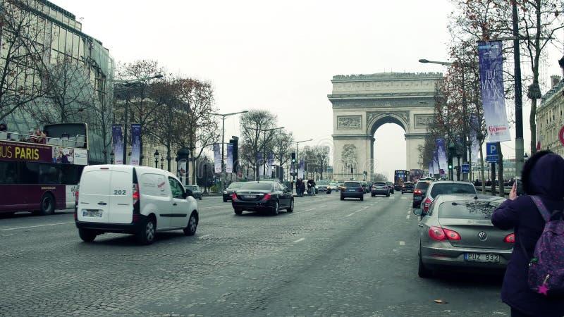ПАРИЖ, ФРАНЦИЯ - 1-ОЕ ДЕКАБРЯ 2017 Улица Champs-Elysees и известный триумфальный свод, Триумфальная Арка Женщина делая фото стоковое фото rf