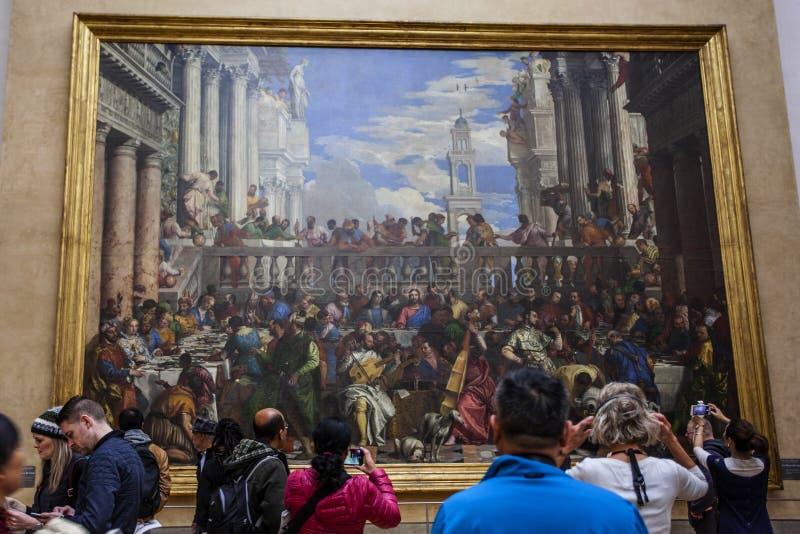 ПАРИЖ, ФРАНЦИЯ - 3-ье октября 2016: Неопознанные посетители посещают картину Paolo Veronese стоковое изображение rf