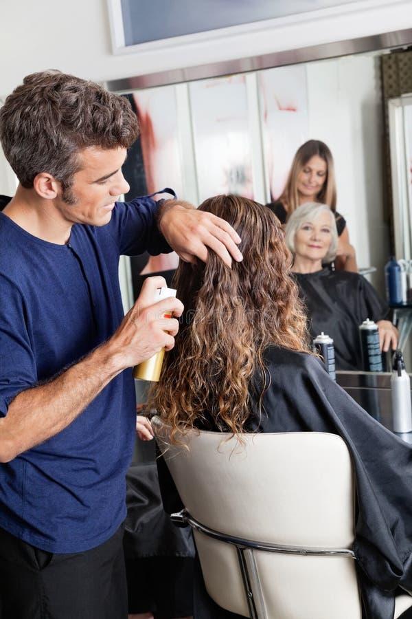 Парикмахеры настраивая волосы клиента стоковое изображение