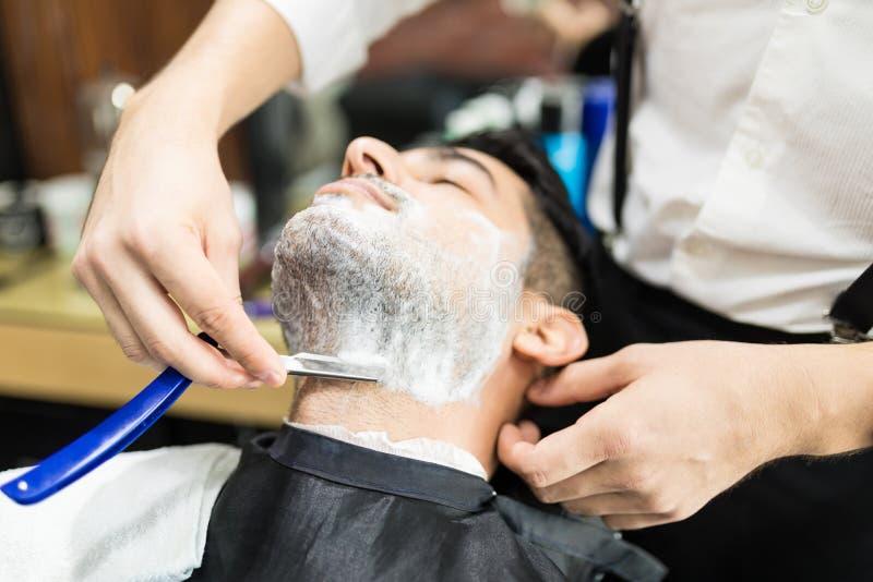 Парикмахер вручает брить стерню ` s человека с прямыми бритвами стоковые фото