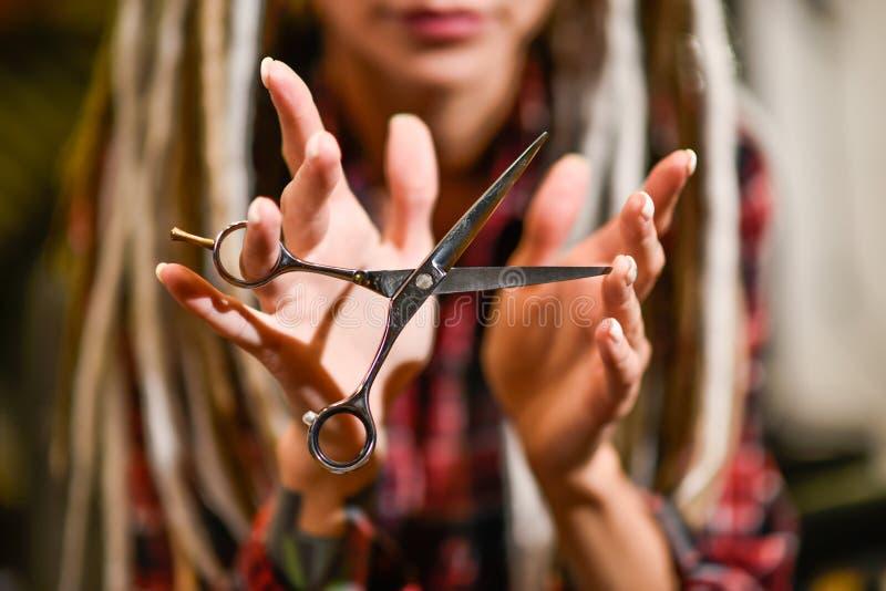 Парикмахер девушки с dreadlocks держа ножницы в конце-вверх руки стоковые изображения rf