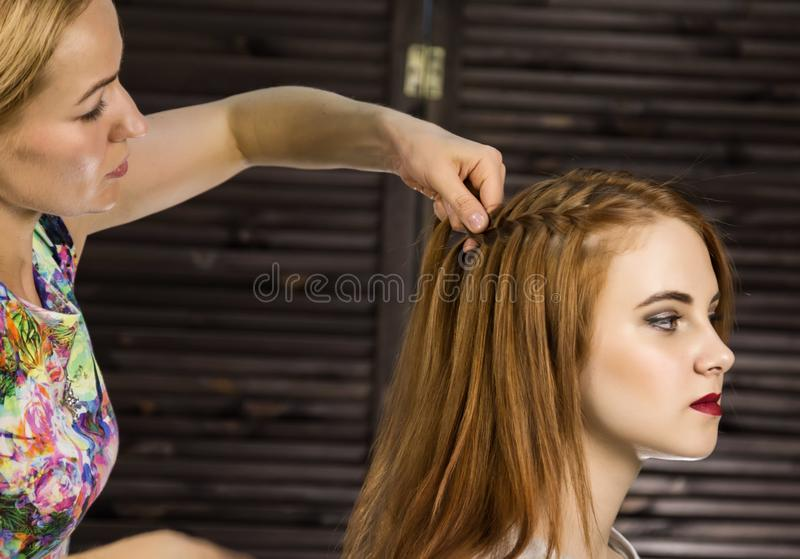 Парикмахер делает стиль причёсок для молодой женщины для того чтобы сплести оплетки Красота и свадьба концепции стоковая фотография rf