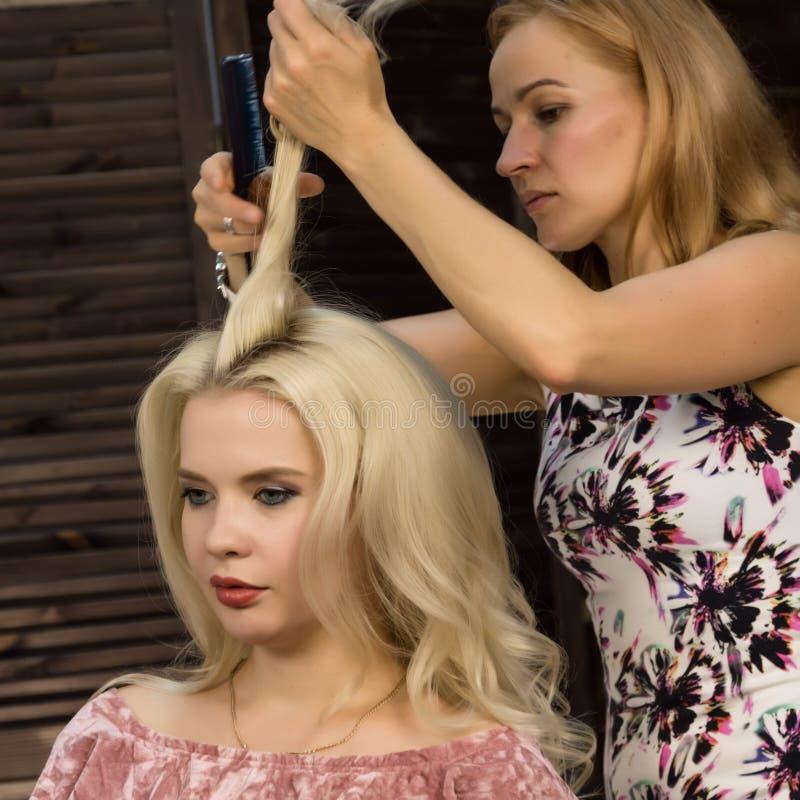 Парикмахер делает стиль причёсок для роскошной белокурой женщины coiffure в форме большой скручиваемости Стиль причёсок свадьбы к стоковое изображение rf