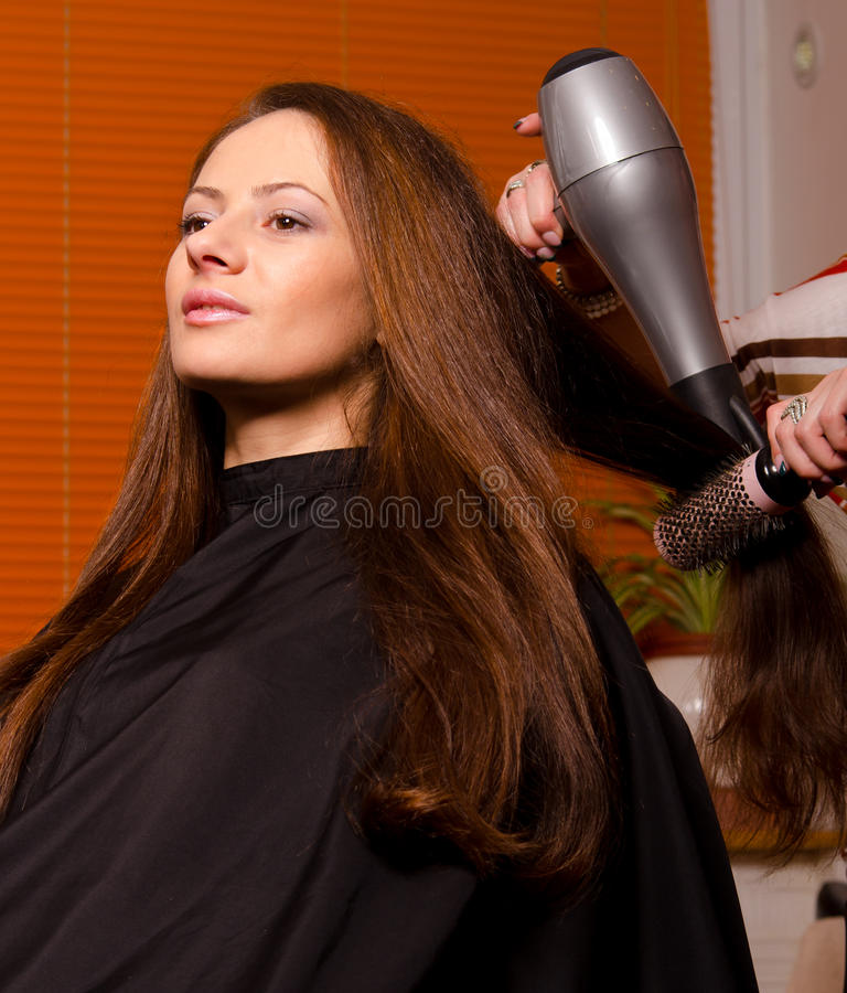 Парикмахер делая волосы красивой девушки стоковые изображения rf