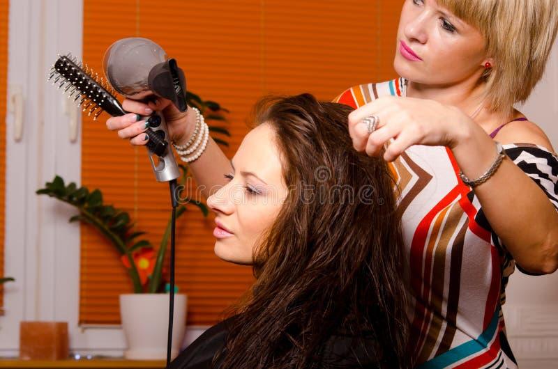 Парикмахер делая волосы красивой счастливой девушки стоковое фото rf