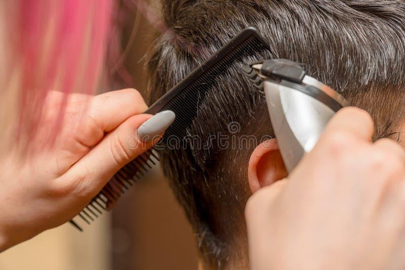 Парикмахер женщины режет волосы человека с триммером электрического клипера стоковое фото rf