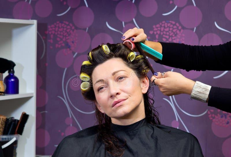 Парикмахер кладя ролики в волосы женщины стоковые фотографии rf