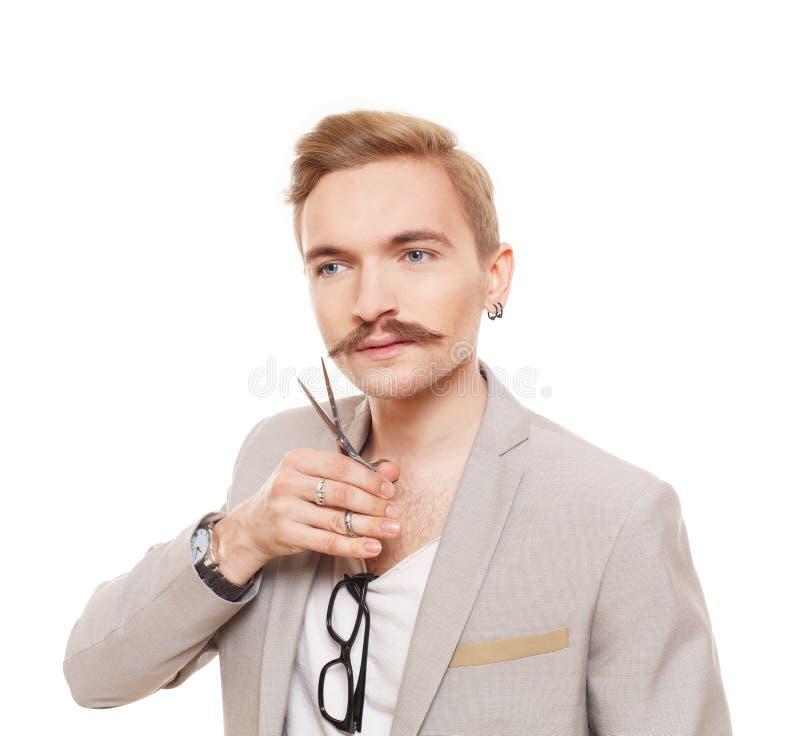 Парикмахер, нося куртка, представляя с ножницами Гай режа его усик стоковая фотография