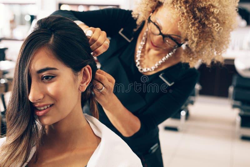 Парикмахер работая на женщине & x27; волосы s на салоне стоковые изображения rf