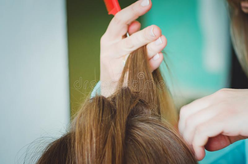 Парикмахер расчесывает ее волосы к клиенту Руки, конец-вверх стоковое фото rf