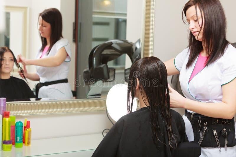 Парикмахер расчесывая клиента женщины волос в салоне красоты парикмахерских услуг стоковые изображения
