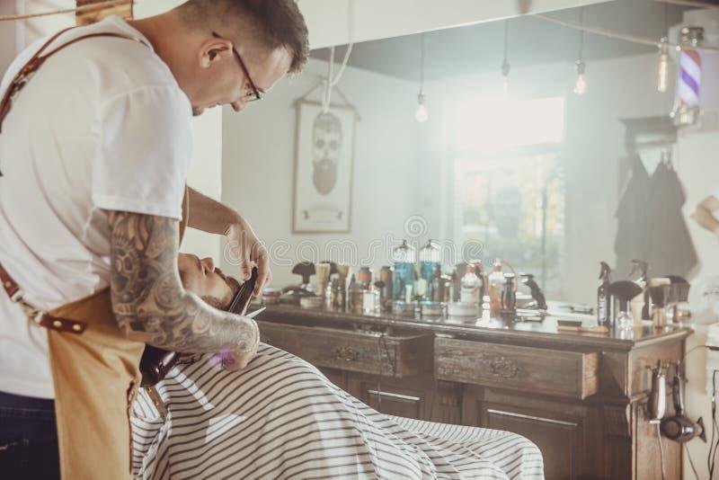 Парикмахер режет бороду ` s клиента в его парикмахерской стоковые изображения rf