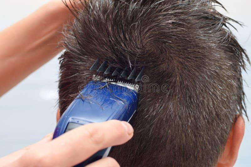 парикмахер стрижет волосы на верхней части головы, закрывает стоковое фото rf