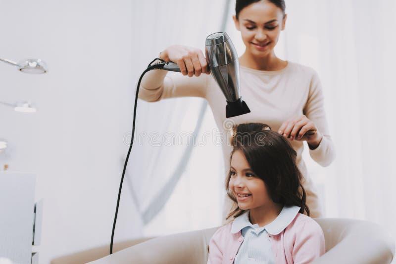 Парикмахер сушит девушку фена волос красивую стоковые фото