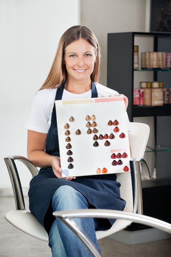 Парикмахер с каталогом цвета на салоне стоковое изображение
