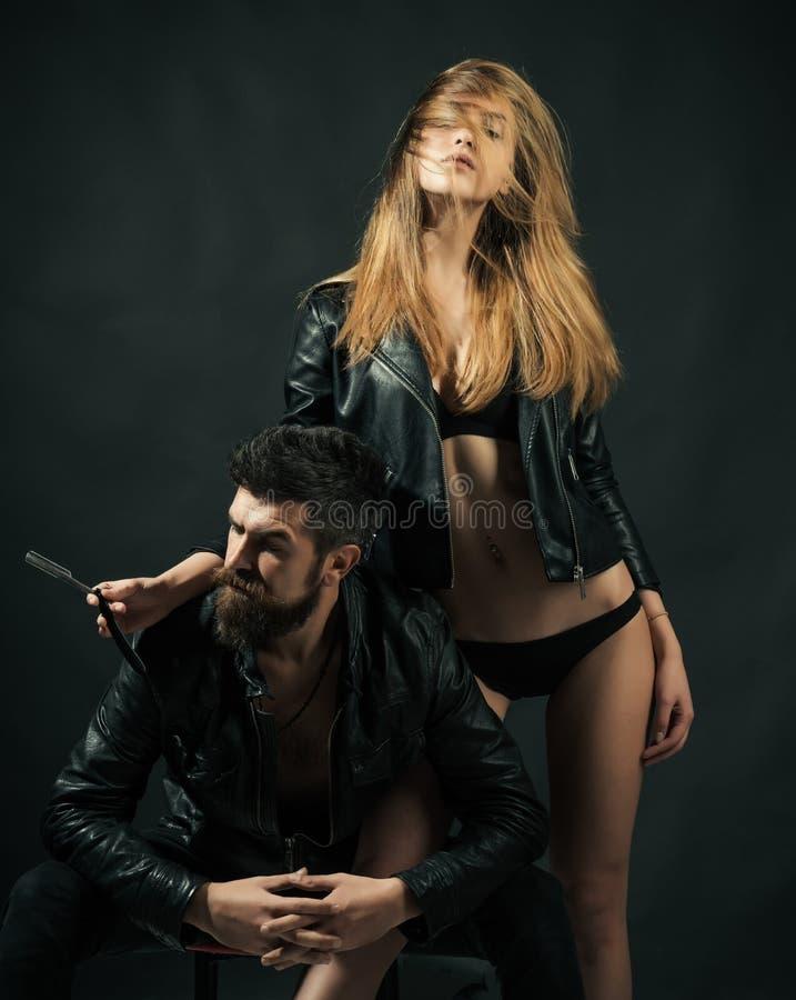 Парикмахер с прямой бритвой работает на стрижке Битник с бородой и сексуальной девушкой держит прямую бритву Концепция парикмахер стоковое изображение