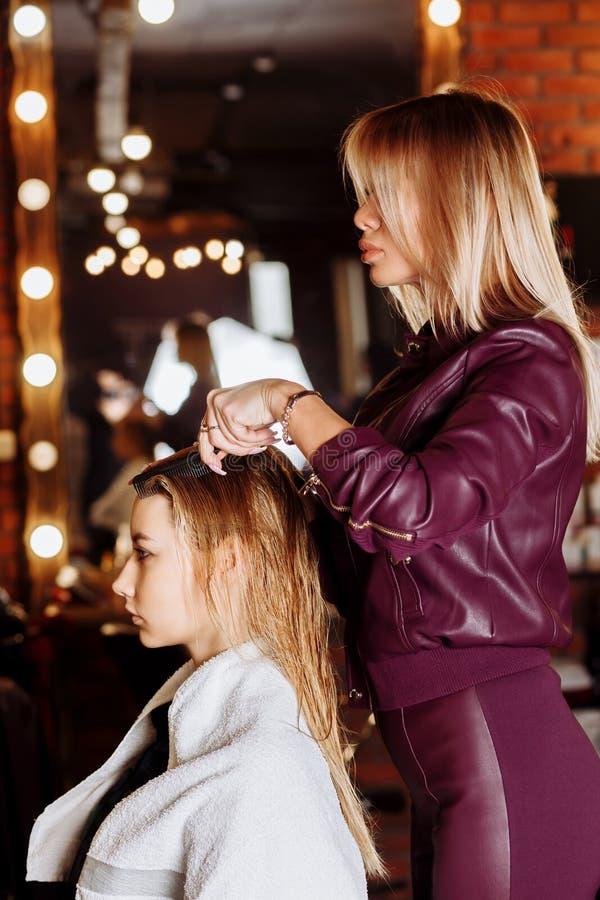 Парикмахер чистя влажные волосы щеткой красивой молодой белокурой женщины в салоне красоты после мыть волосы Здоровье волос, сало стоковые фотографии rf