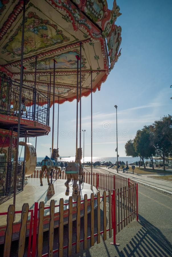 Парк атракционов в центре thessaloniki лошади забавляются для детей для того чтобы сделать некоторые круги стоковые изображения