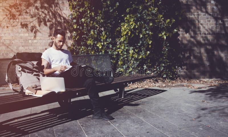 Парк города белой футболки молодого человека нося сидя и книга чтения Изучающ в университете, работая новый проект стоковые фото