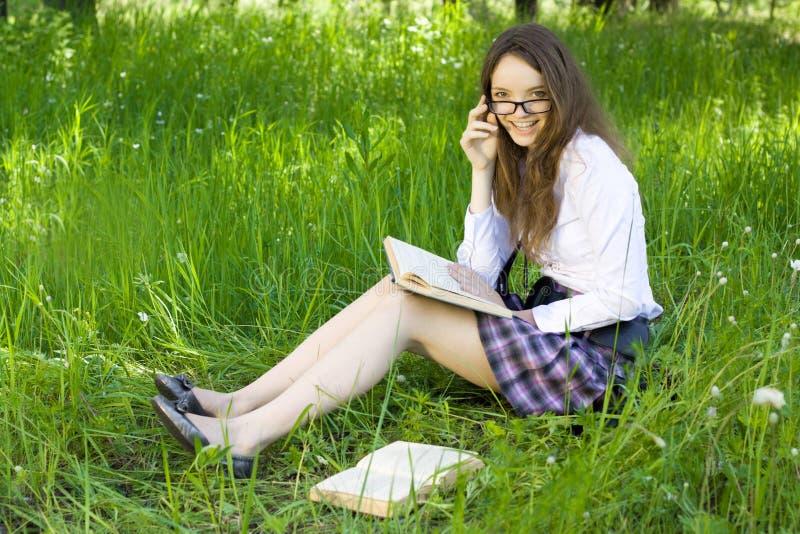 парк книги прочитал школьницу стоковая фотография