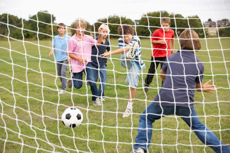 парк мальчиков играя футбол стоковая фотография rf
