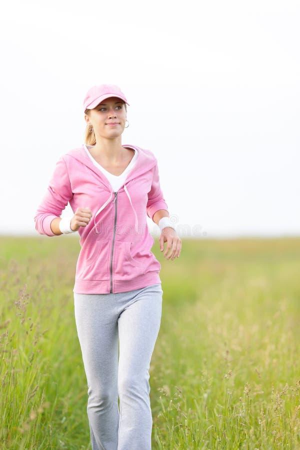 парк поля jogging sportive детеныши женщины стоковое изображение