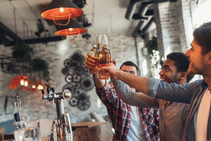 Парни выпивая пиво для встречи в баре стоковое изображение rf