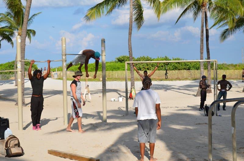 Парни делают весы на песке стоковое фото