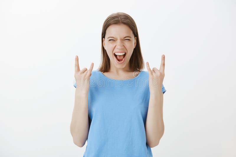 Парни жизней крена n утеса Портрет возбужденной радостной европейской белокурой женщины в голубой футболке, показывая жесты с стоковое изображение