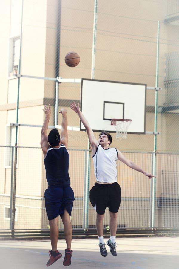 парни играя баскетбольный матч в населенном пункте городского типа стоковые изображения