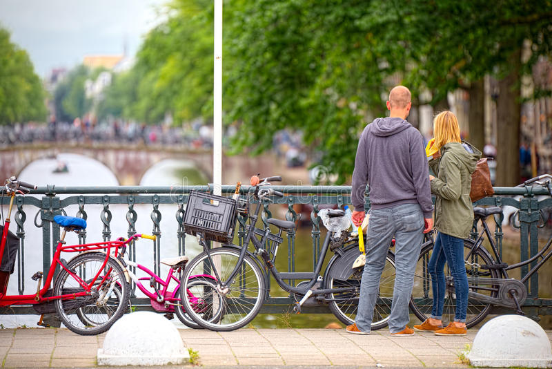 Парни наблюдают каналами Амстердама от моста стоковое изображение rf
