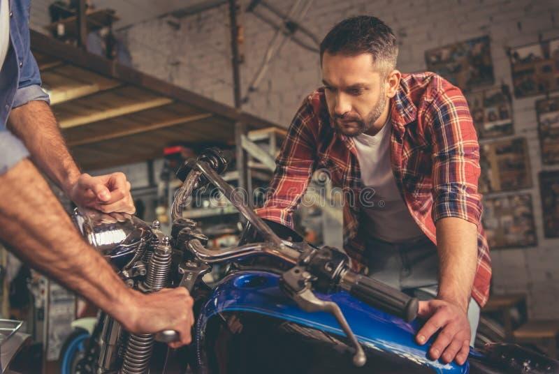 Парни на ремонтной мастерской мотоцилк стоковые изображения