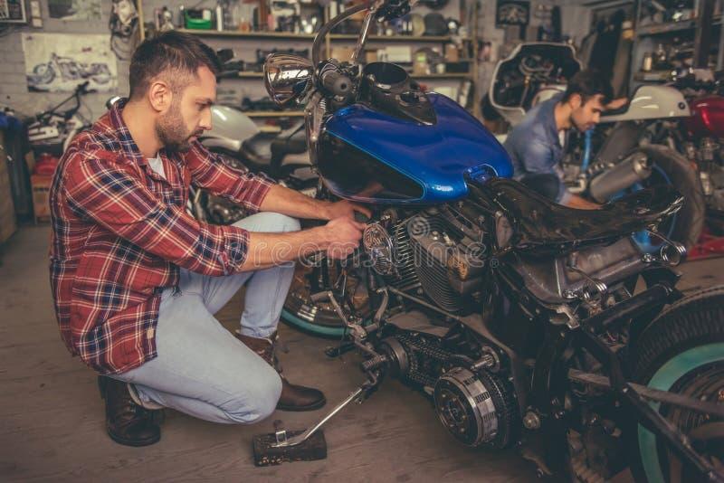 Парни на ремонтной мастерской мотоцилк стоковая фотография