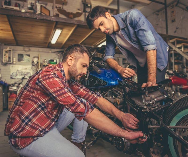 Парни на ремонтной мастерской мотоцилк стоковое изображение