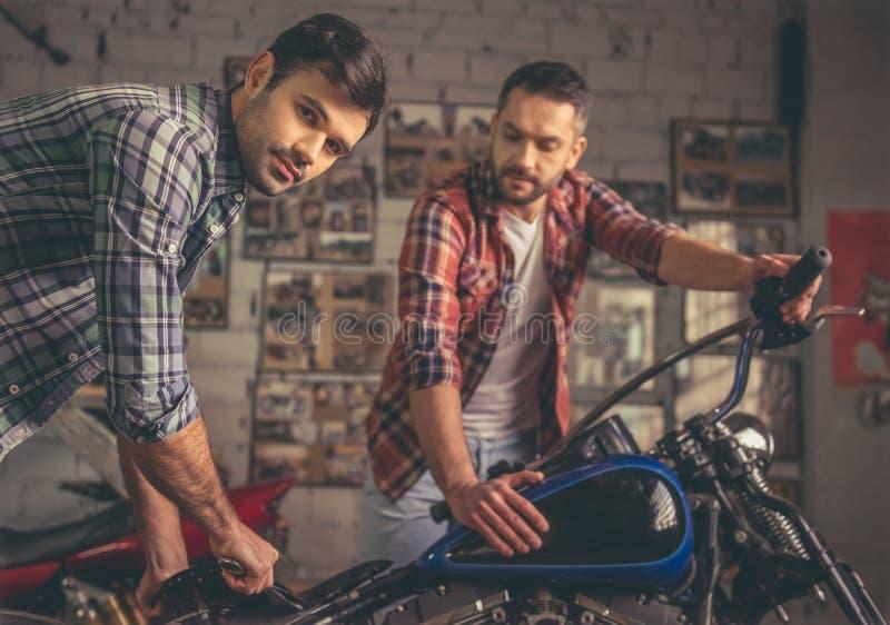 Парни на ремонтной мастерской мотоцилк стоковая фотография rf