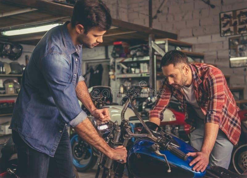 Парни на ремонтной мастерской мотоцилк стоковые фото