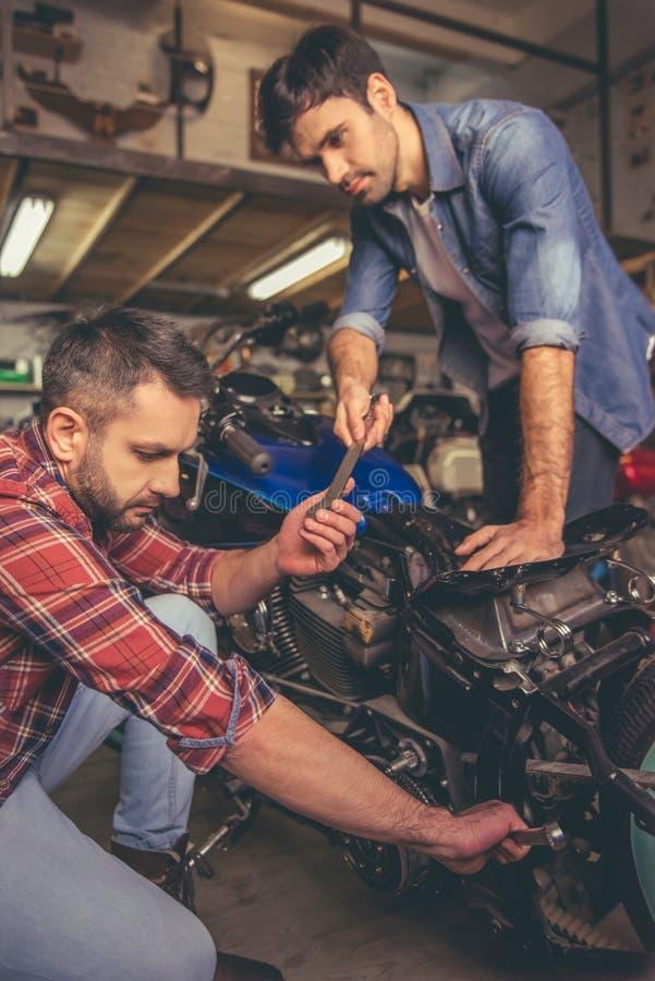 Парни на ремонтной мастерской мотоцилк стоковое фото rf