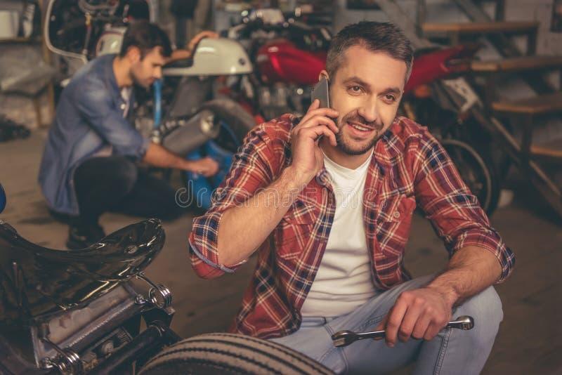 Парни на ремонтной мастерской мотоцилк стоковые изображения rf