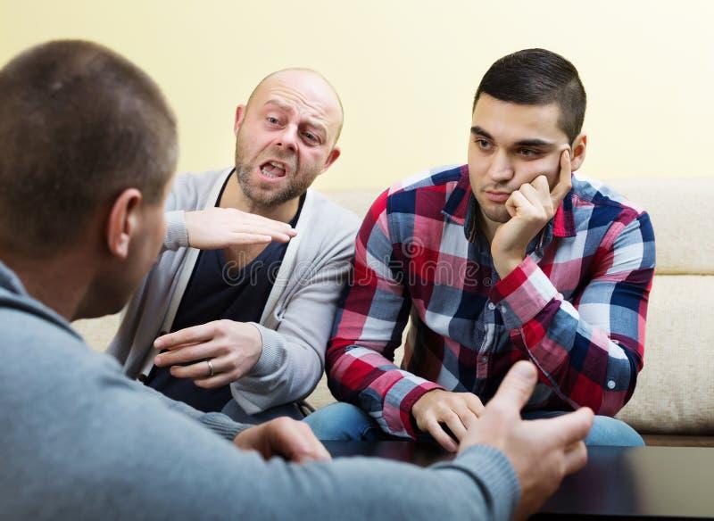 Парни сидя на таблице и деля проблемы стоковое изображение rf